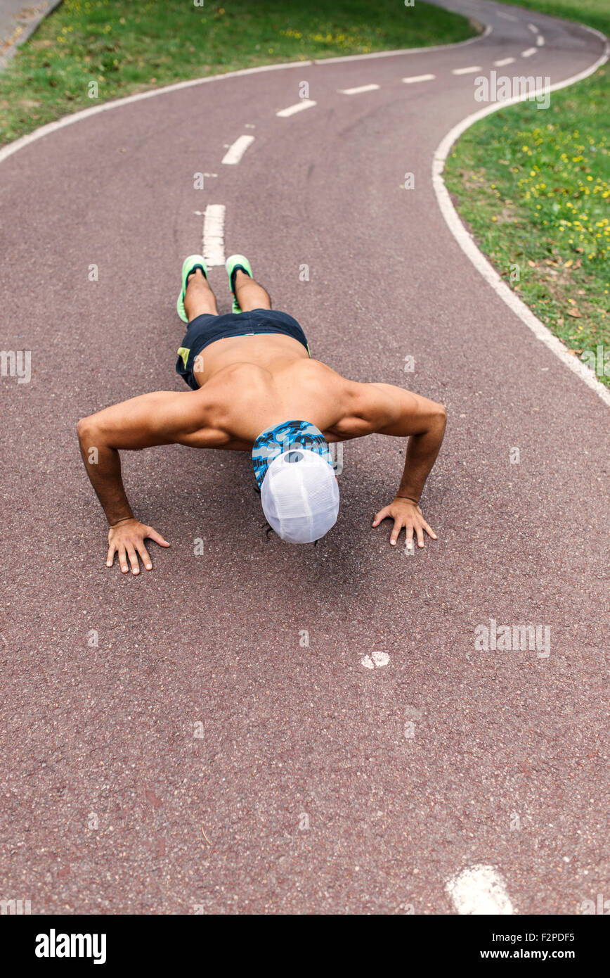 Athletic young man doing pushups in the park - Stock Image