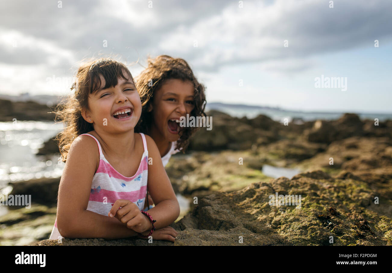 Spain, Gijon, portrait of two laughing little girls at rocky coast - Stock Image