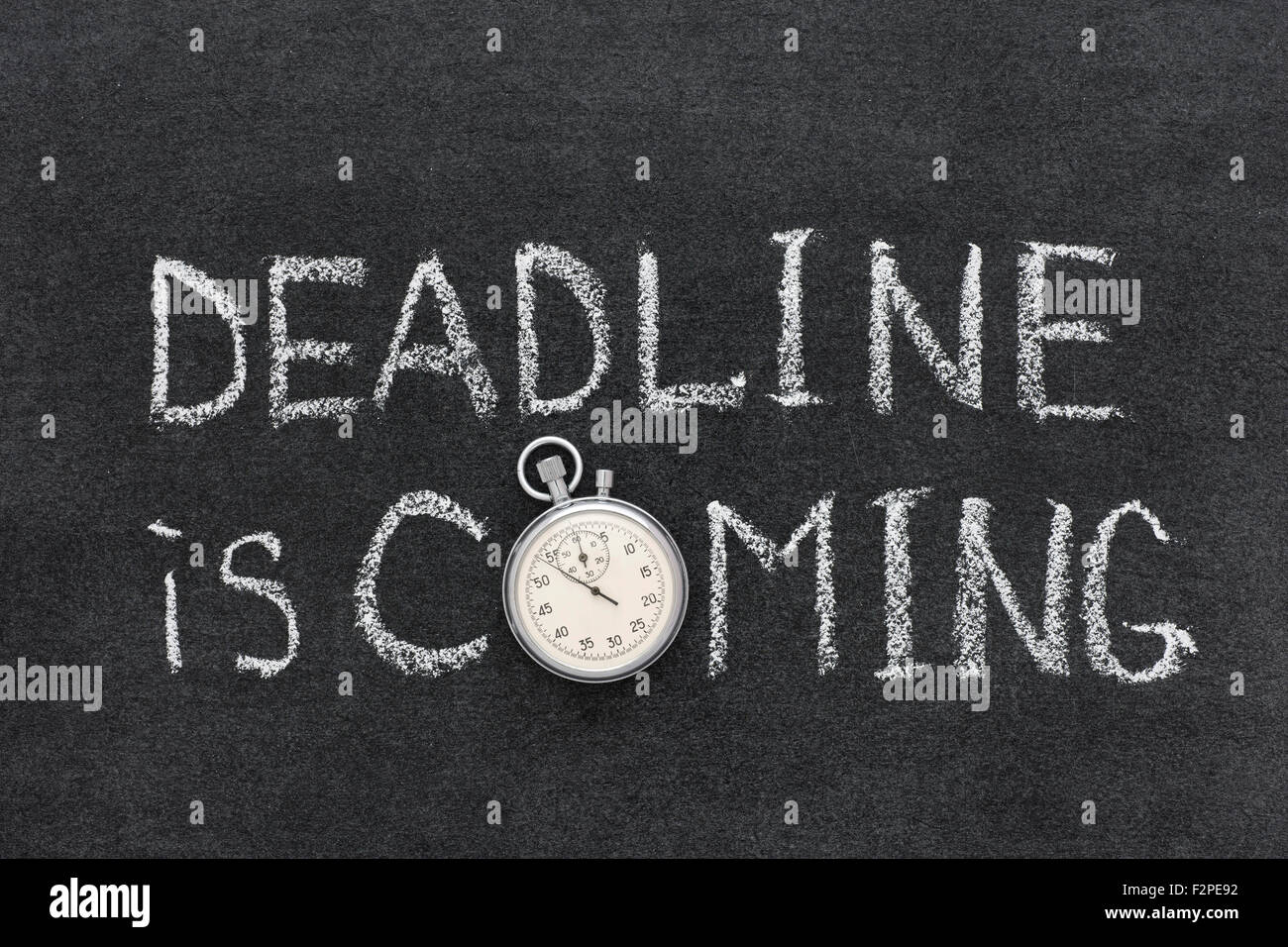 deadline is coming phrase handwritten on chalkboard with vintage precise stopwatch used instead of O - Stock Image