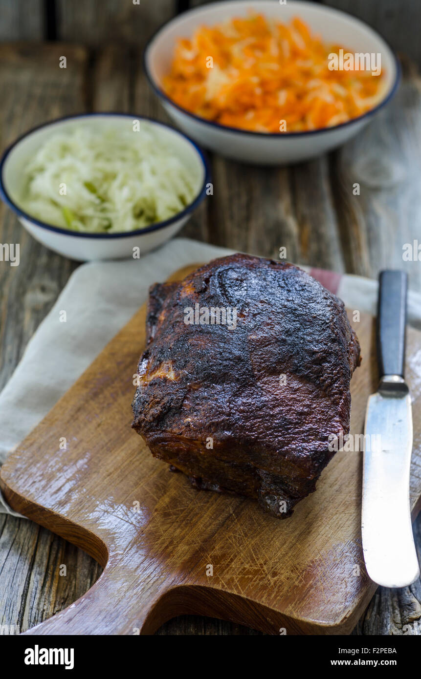 Pulled pork on chopping board, salads in background - Stock Image