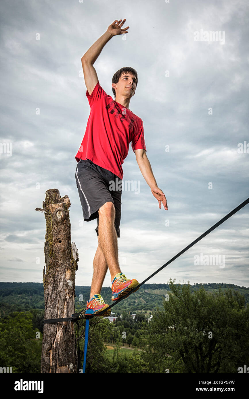 Young man balancing on slackline - Stock Image