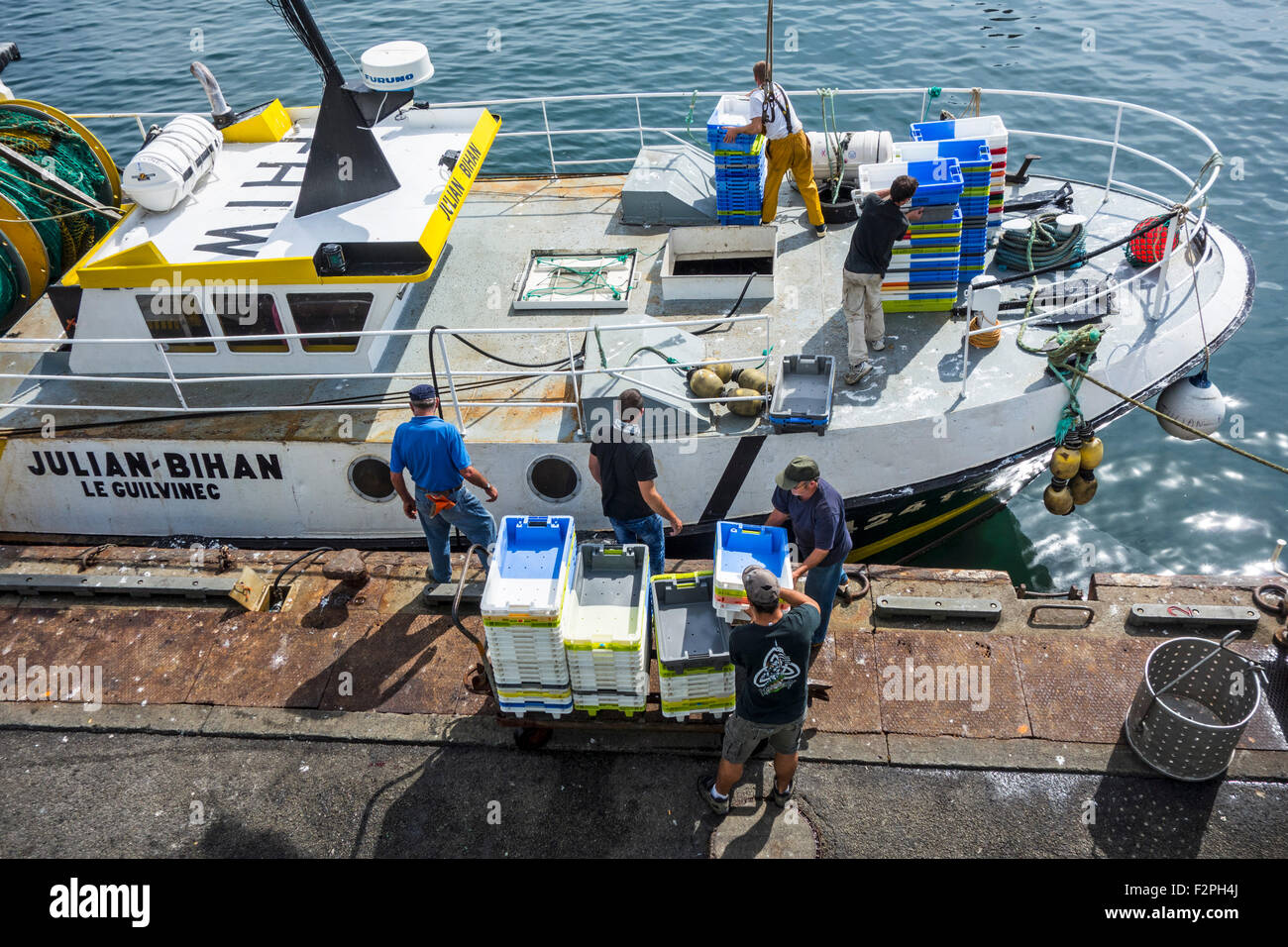 Fishermen on board of fishing boat loading plastic trays along quay of fish auction market in Guilvinec port, Brittany, - Stock Image