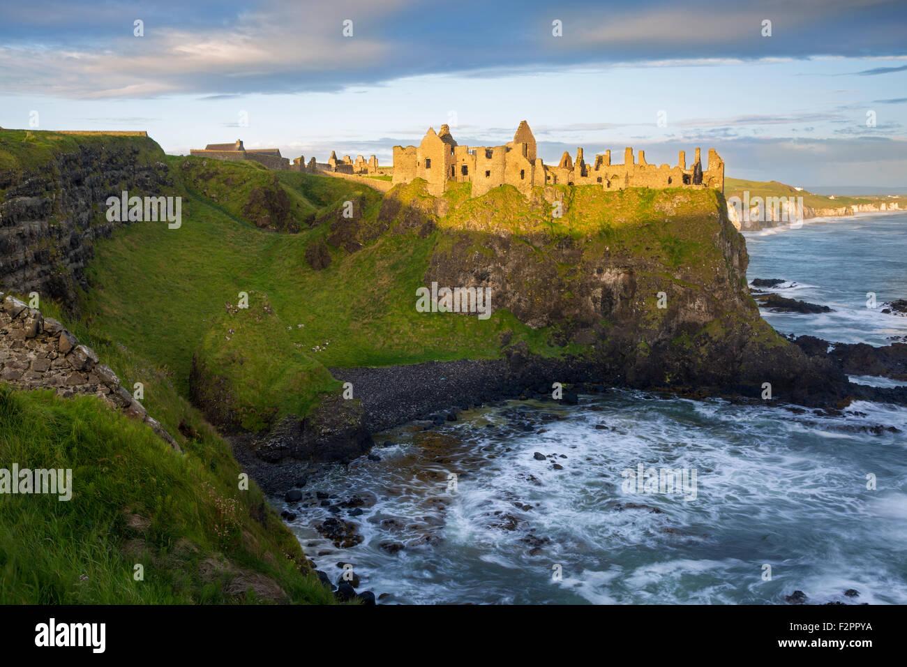Sunrise over Dunluce Castle along northern coast of County Antrim, Northern Ireland, UK Stock Photo