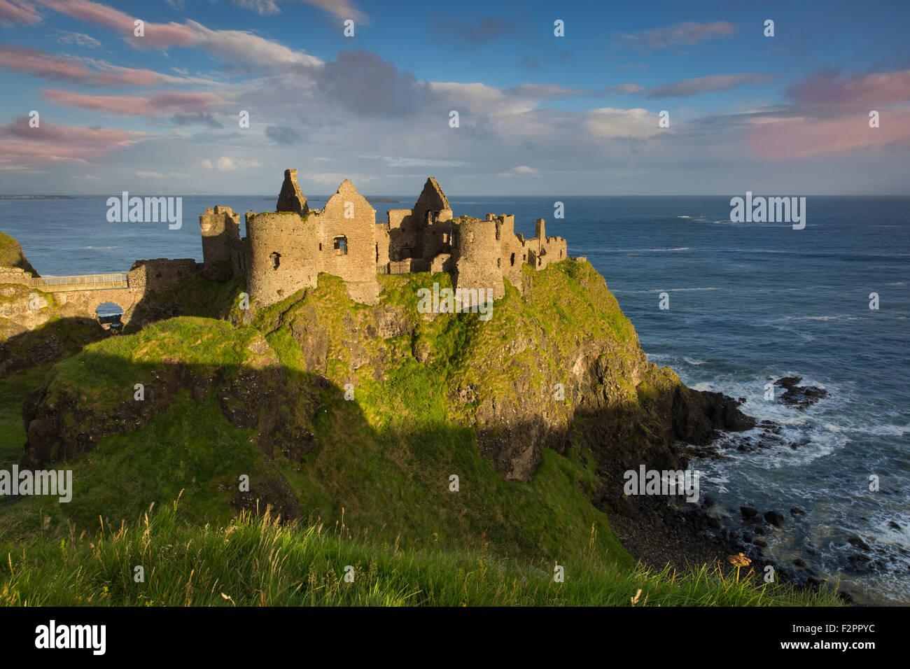 Sunrise over Dunluce Castle along northern coast of County Antrim, Northern Ireland, UK - Stock Image