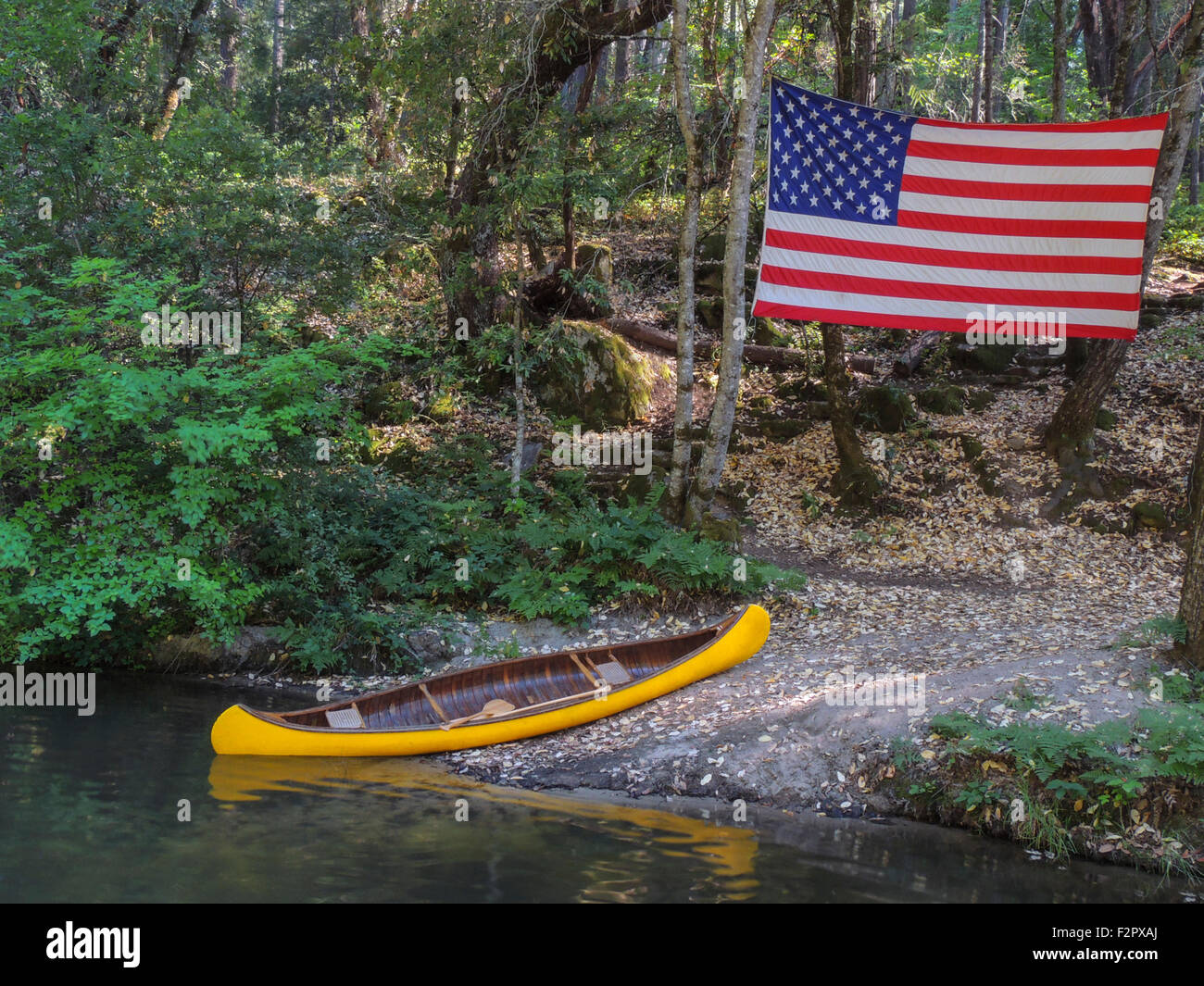 American Flag and Classic canoe, built in 1919, Celebrates Independence Day July 4th in the Sierra foothills , Northern - Stock Image