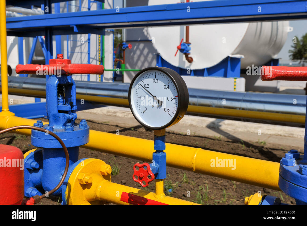 Pressure meter and red faucet with steel yellow pipe in natural gas treatment plant in bright sunny summer day - Stock Image
