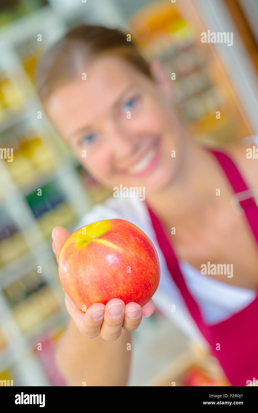Shop worker holding an apple - Stock Image