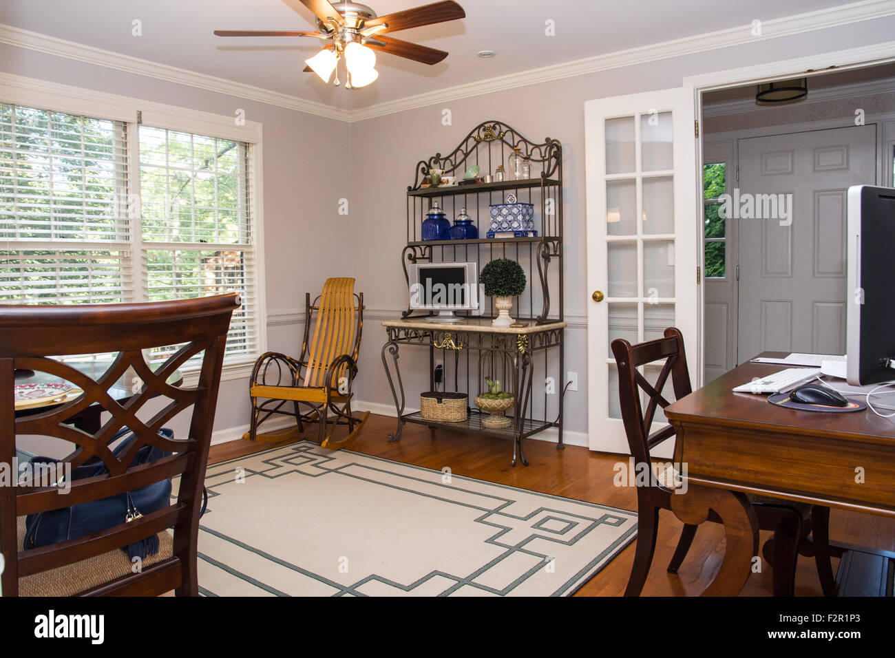 A Wrought Iron Bakeru0027s Rack, A Rocking Chair, And A Desk And Chair Are An  Inviting Setting In A Warm, Bright Breakfast Room.