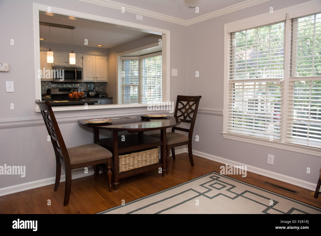 A small dining table is an inviting setting in a warm, bright breakfast room. - Stock Image