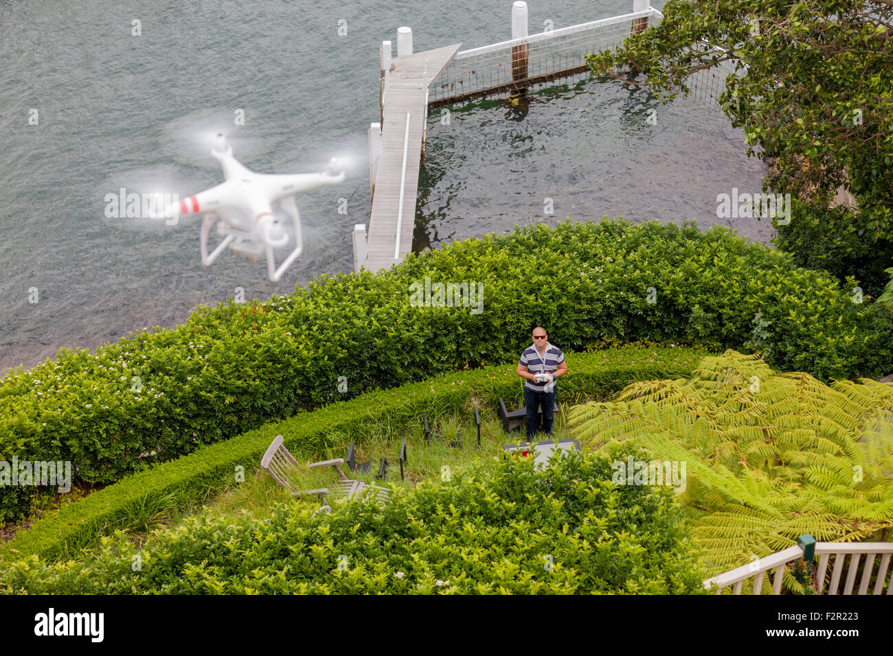 A view from above of a flying drone with a gimbal and camera attached. - Stock Image