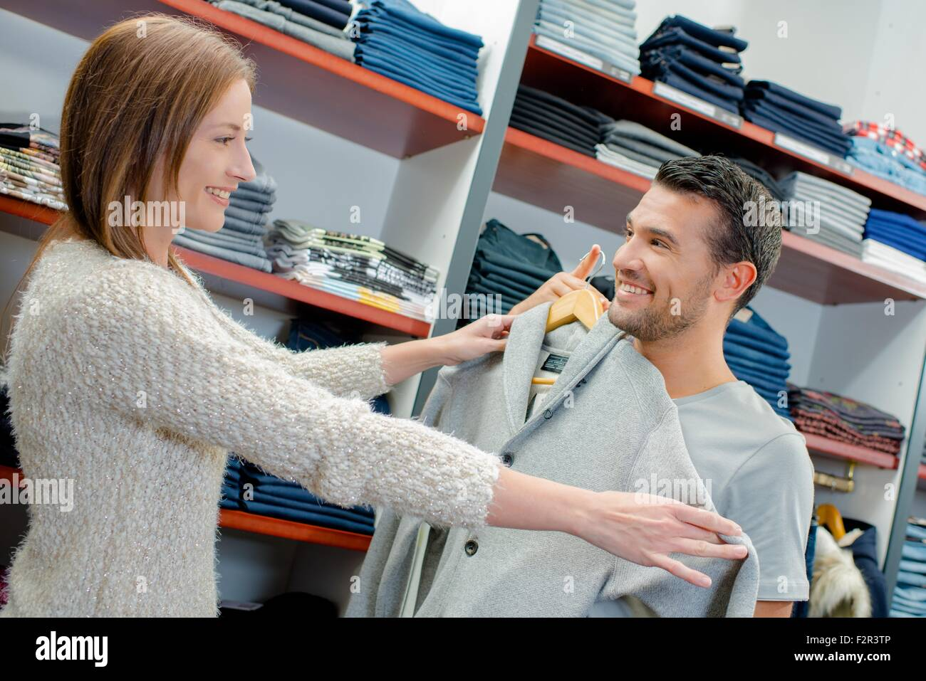 Buying clothes for her boyfriend - Stock Image