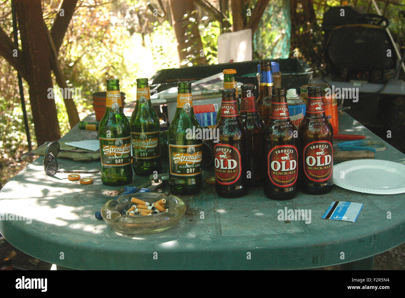 Outdoor table containing empty beer bottles and ash tray of cigarette butts. - Stock Image