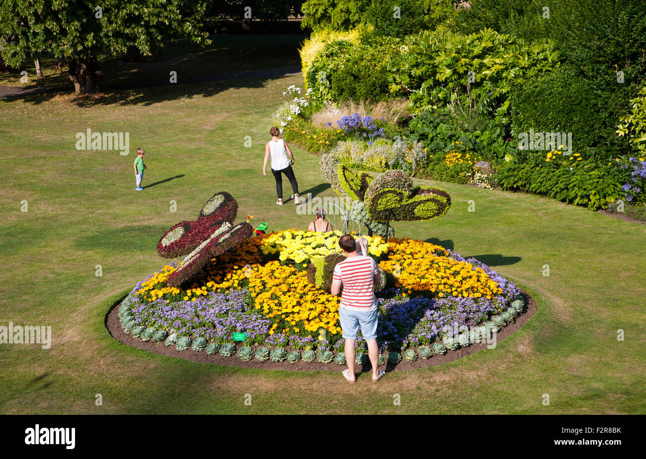 Family enjoying floral display of butterflies in Parade Gardens public park in city centre of Bath, Somerset, England, - Stock Image