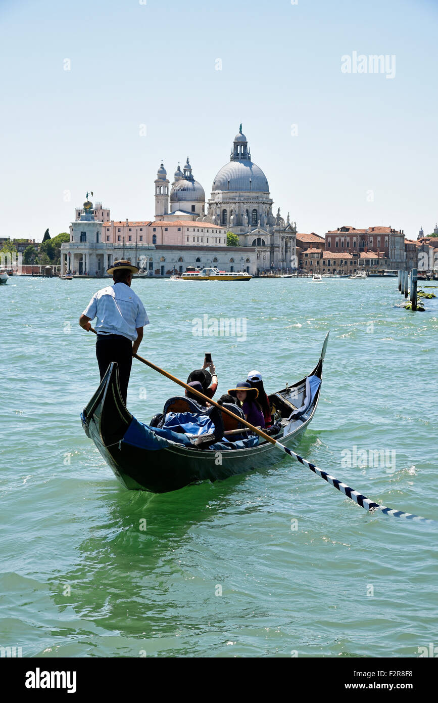 Gondola and gondolier with tourists in front of the church of Santa Maria della Salute, Venice, Venezia, Veneto, - Stock Image