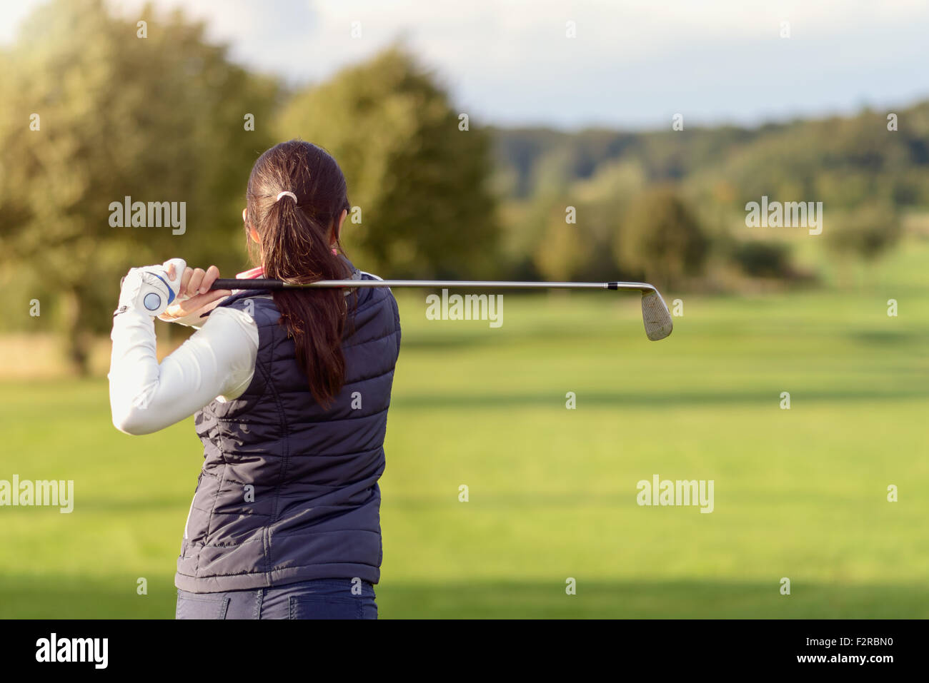 Female golfer striking a golf ball on a golf course, half body rear view looking down the golf course - Stock Image