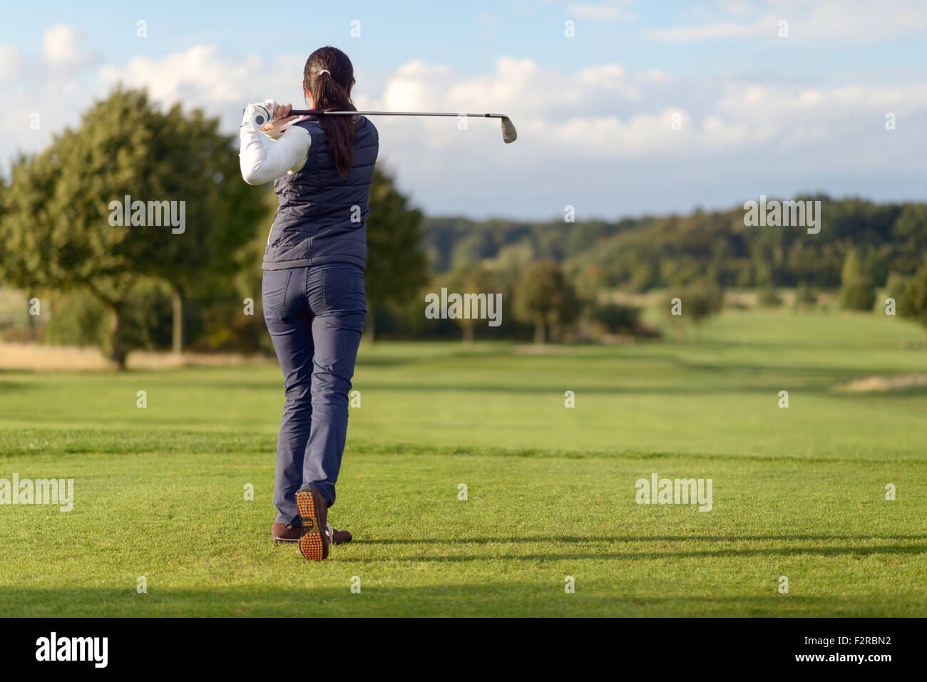 Female golfer striking a golf ball on a golf course, full body rear view looking down the golf course - Stock Image