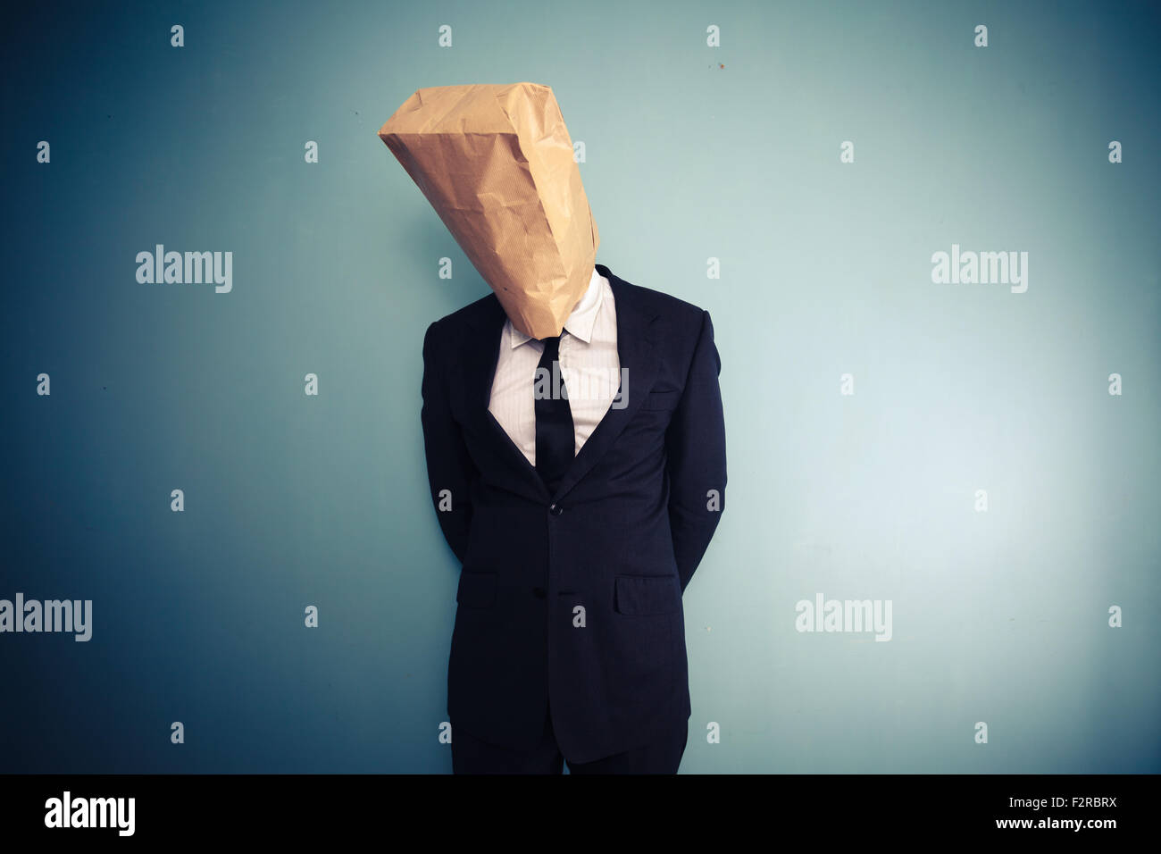 sad and ashamed businessman with bag over head - Stock Image