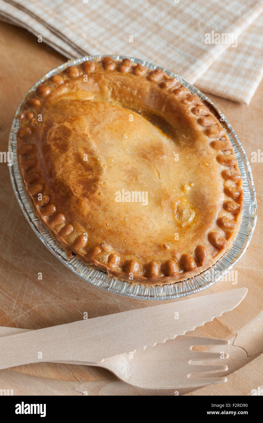 Savoury meat or steak pie takeaway in a foil tray with wooden cutlery - Stock Image