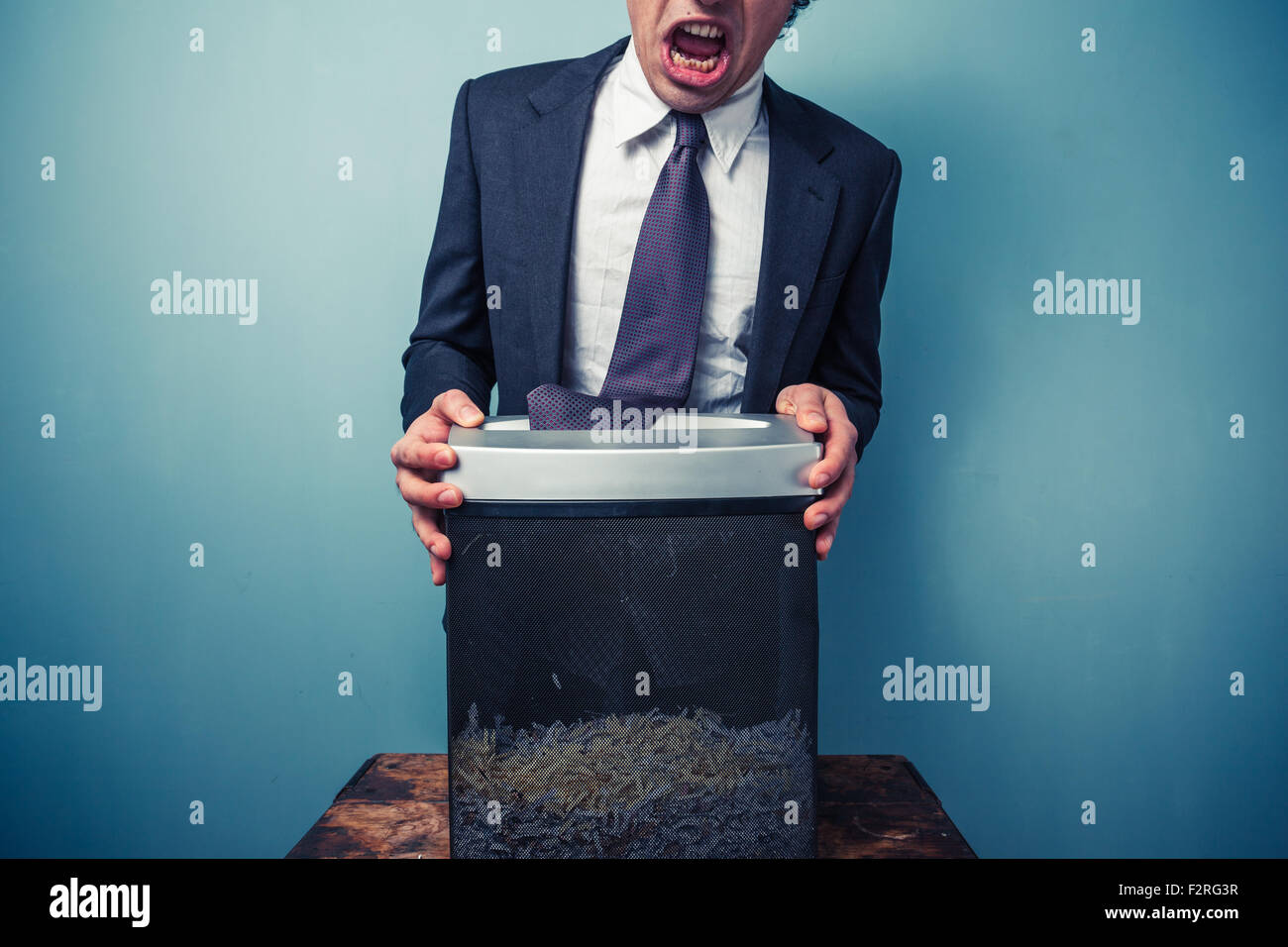 Businessman has got his tie stuck in a paper shredder - Stock Image