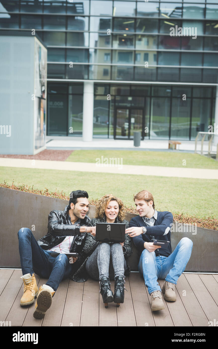 Multiracial business people working outdoor sitting on the ground, connected with technological devices like tablet - Stock Image