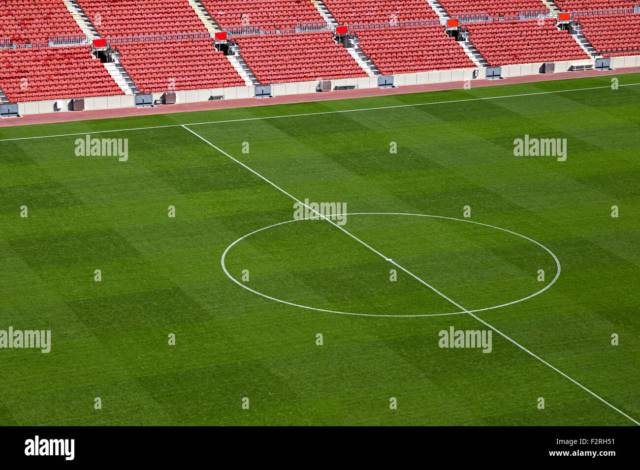 empty soccer stadium with red seat shells and green field - Stock Image