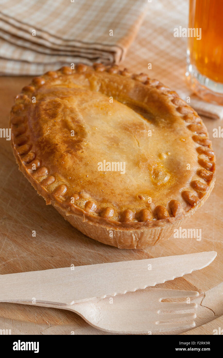 Savoury meat or steak pie takeaway with wooden cutlery - Stock Image