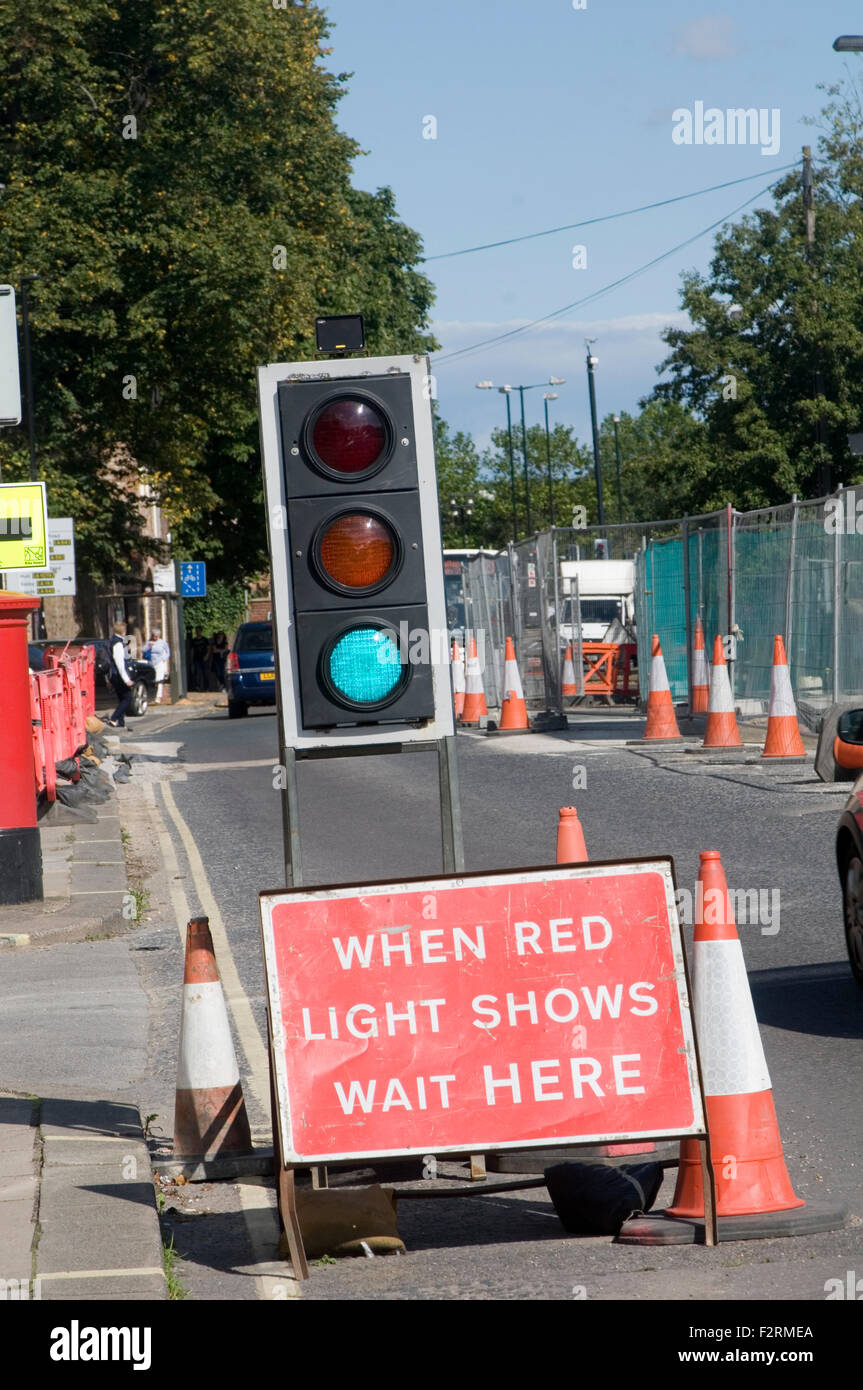 temporary traffic lights roadworks road roads works work light green lights delay delays - Stock Image