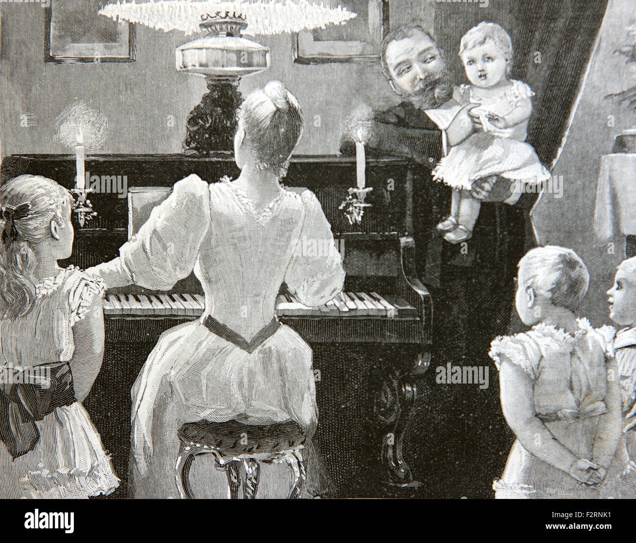 Edwardian family having a sing song around the piano. - Stock Image