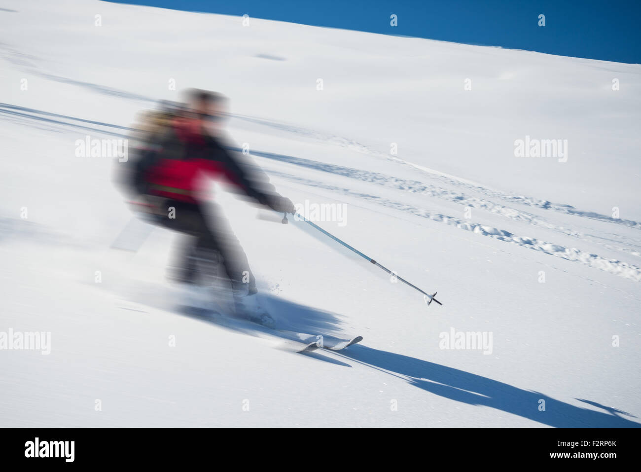 One person skiing downhills off piste on snowy slope in the italian Alps, with bright sunny day of winter season. - Stock Image