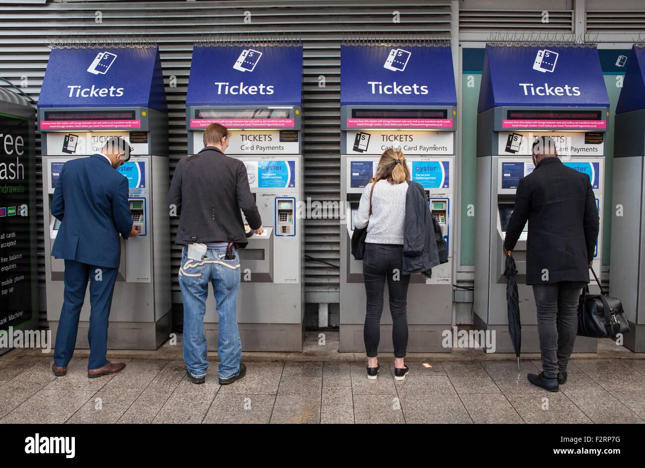 Rail passengers use self-service ticket machines at London Bridge train station - Stock Image