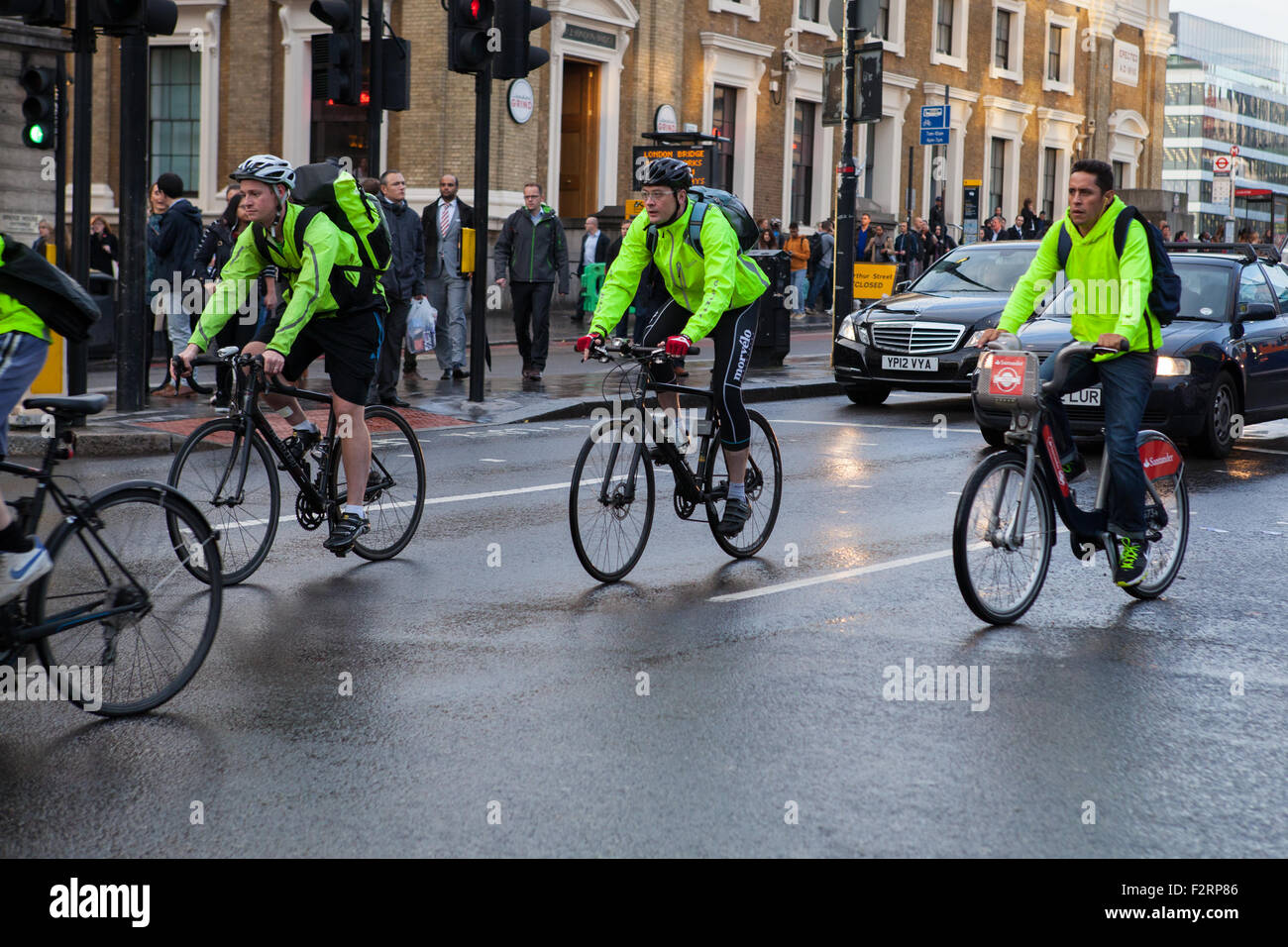 Cyclists wearing high-visibility clothing riding in London Stock Photo