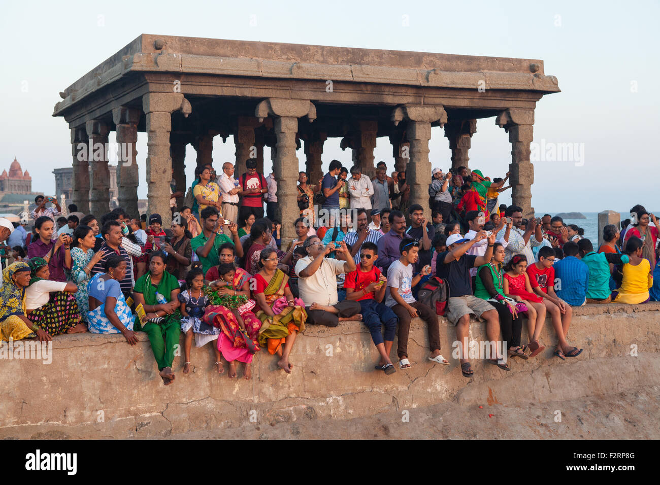 Pilgrims and devotees watch and take photographs from a temple as the sun sets at Kanyakumari - Stock Image
