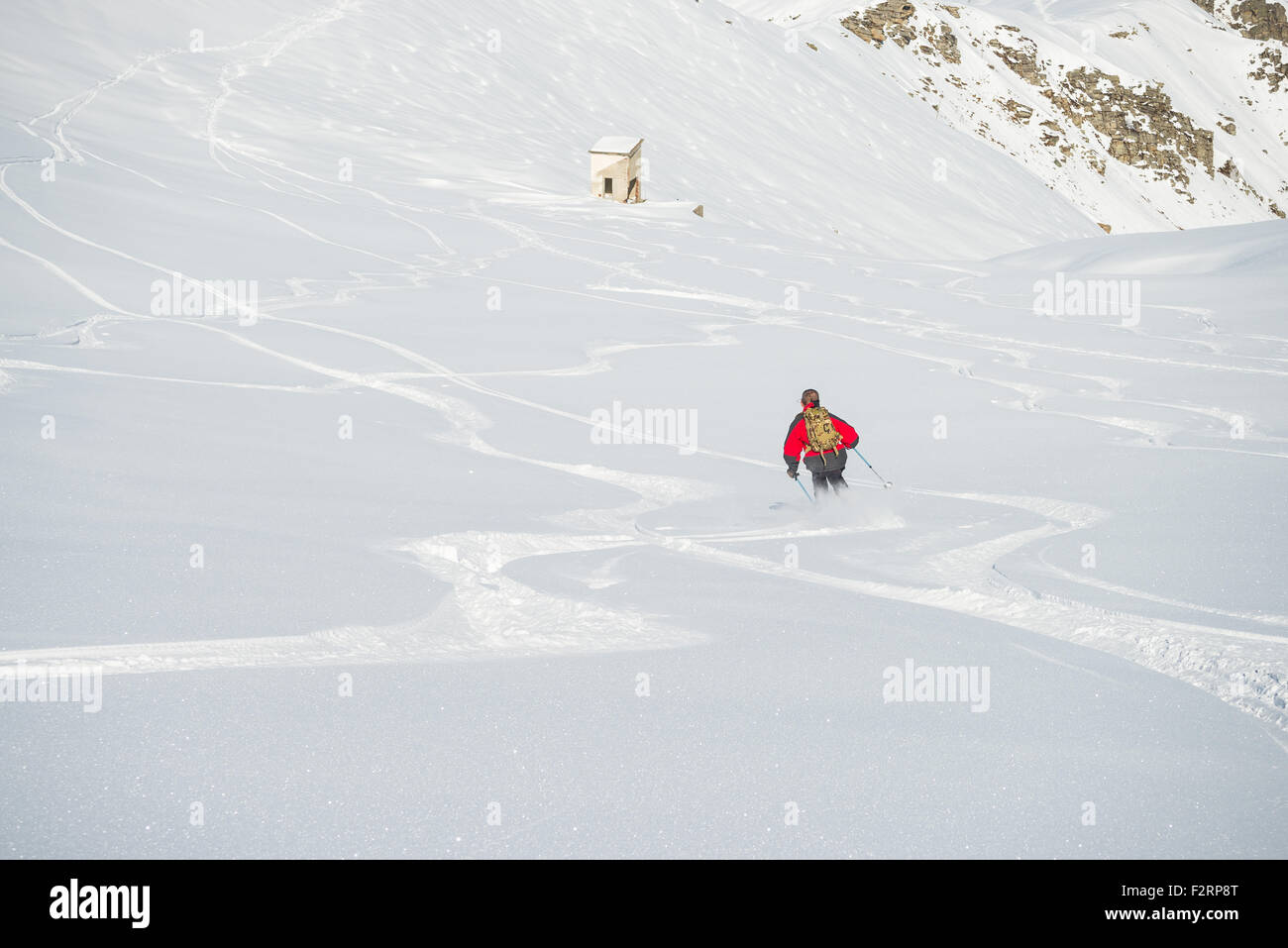 One person skiing downhills off piste on snowy slope in the italian Alps, with bright sunny day of winter season. Stock Photo