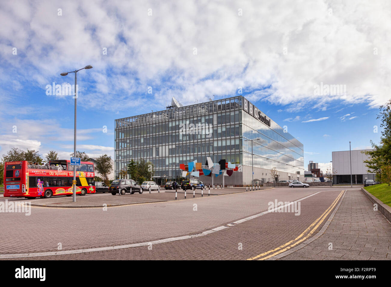 Headquarters of BBC Scotland, Glasgow. Outside are taxi cabs and a tour bus. - Stock Image