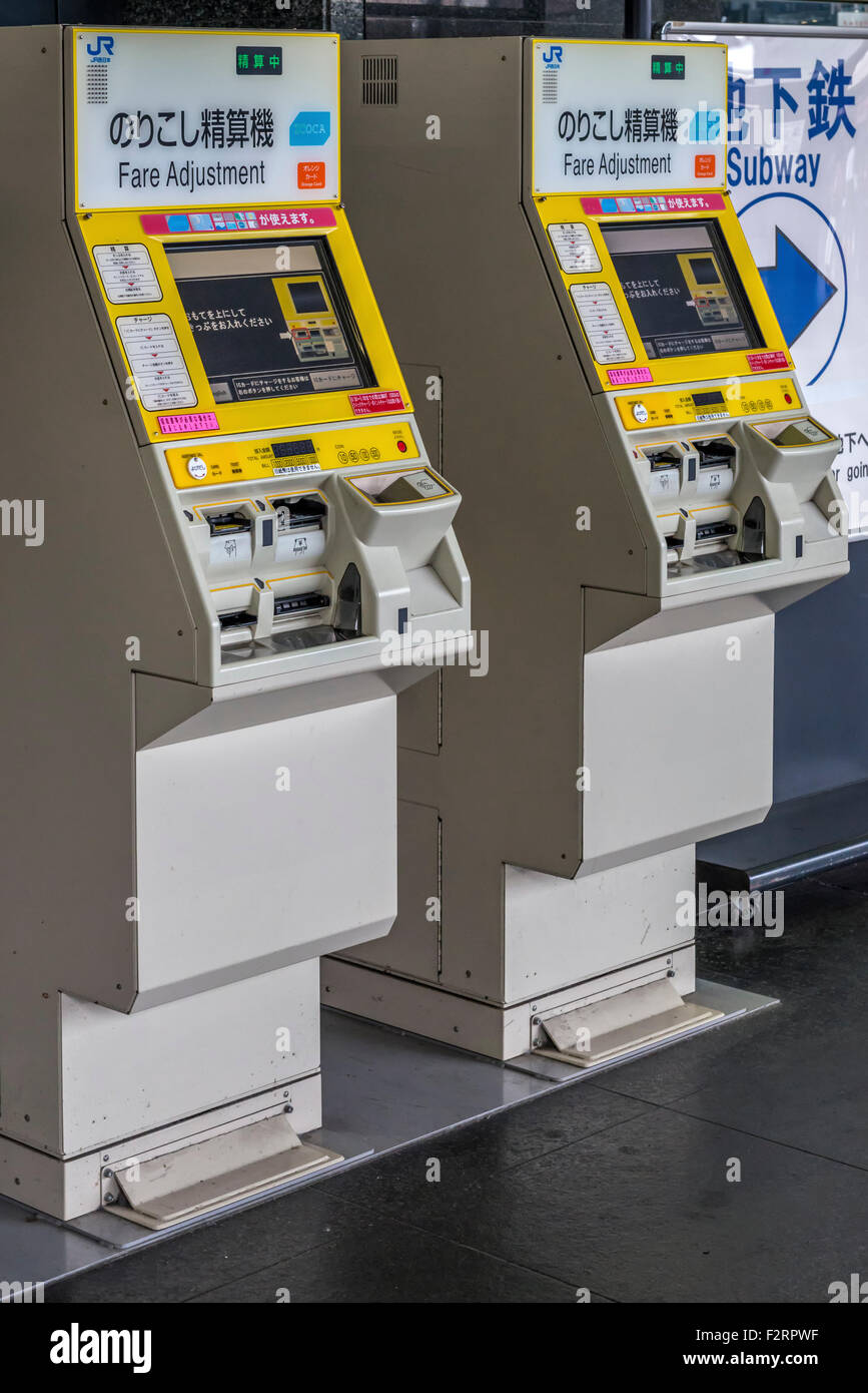 Fare adjustment machines allowing passengers to pay for excess or additional fares on a Japanese station platform - Stock Image