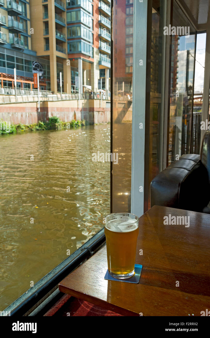 The river Irwell from inside the Mark Addy pub, Salford, Manchester, England, UK, with a pint of beer in a glass - Stock Image