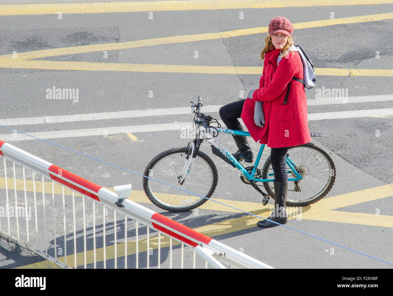 Girl on a bike waiting at the level crossing gates in England, UK. - Stock Image