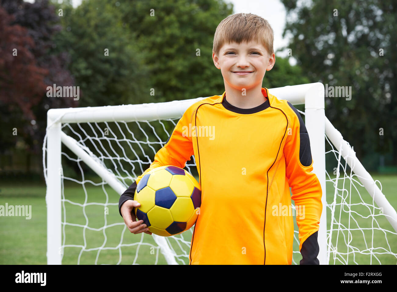 Portrait Of Goal Keeper Holding Ball On School Soccer Pitch - Stock Image