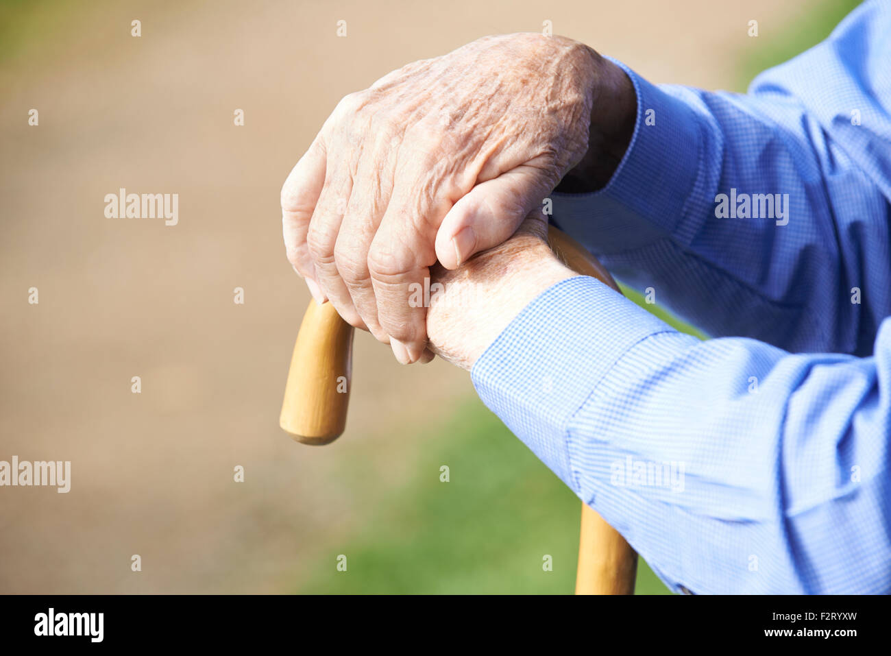 Close Up Of Senior Man's Hands Resting On Walking Stick - Stock Image