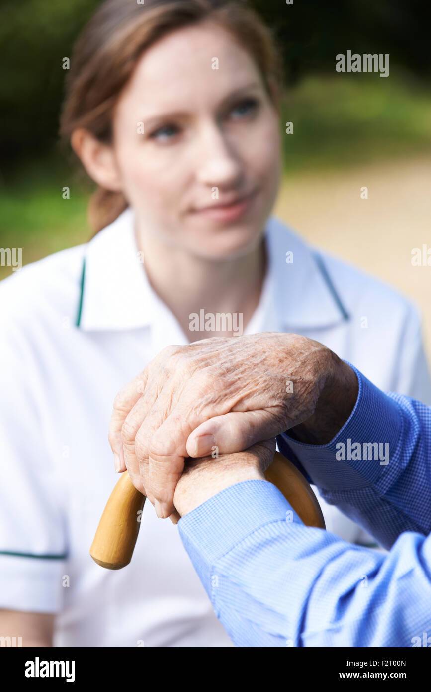 Senior Man's Hands Resting On Walking Stick With Care Worker In Background - Stock Image