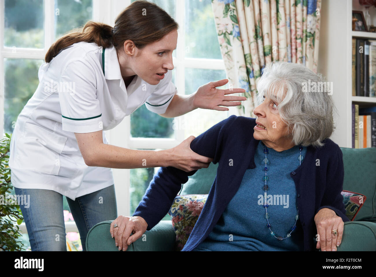 Care Worker Mistreating Senior Woman At Home - Stock Image