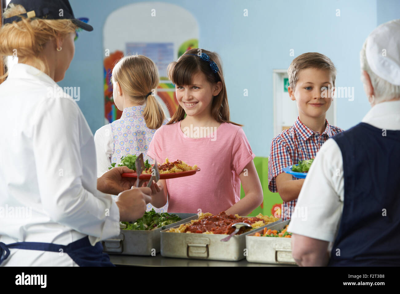Pupils Being Served With Healthy Lunch In School Canteen - Stock Image