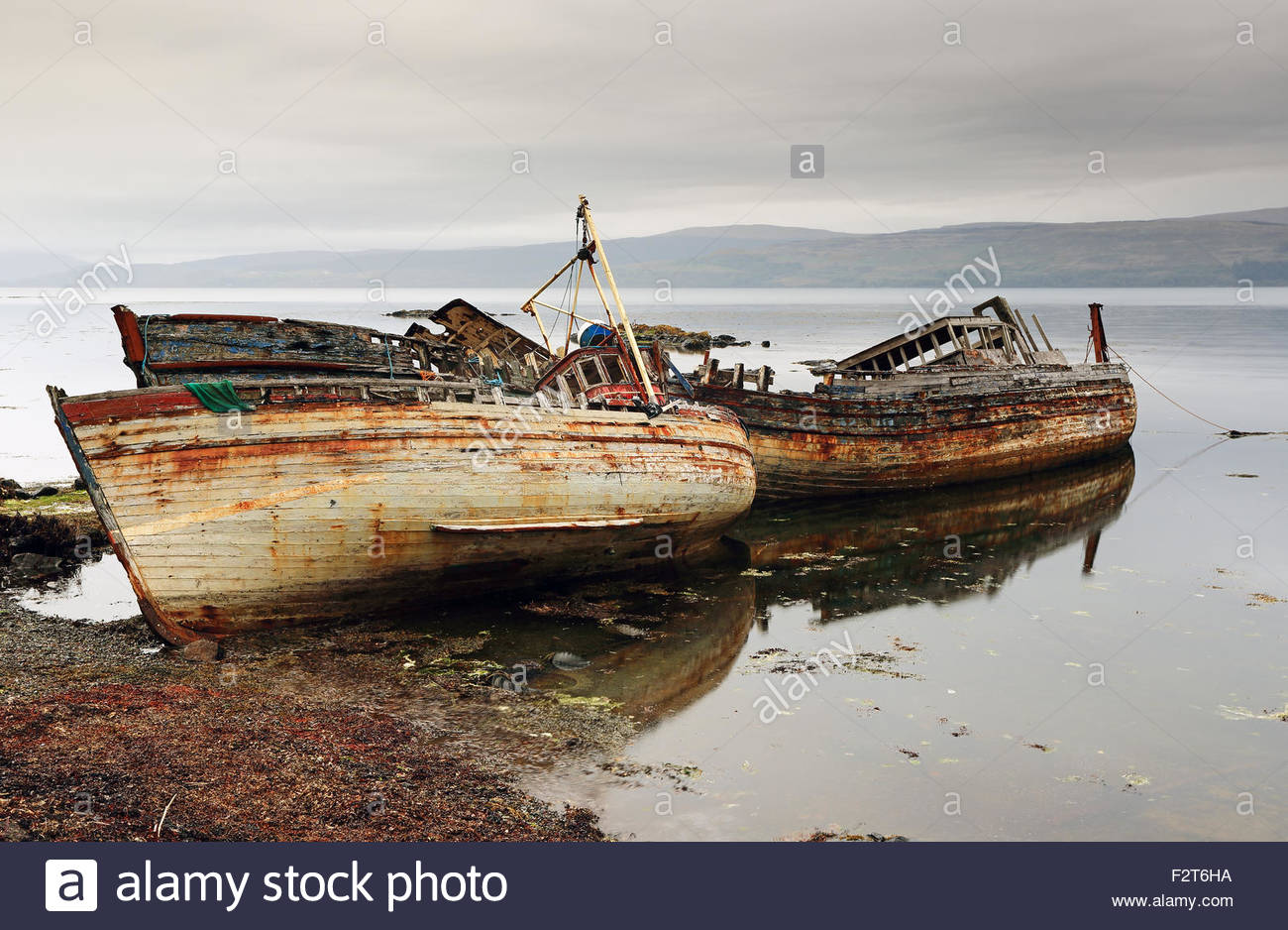 Two fishing boat ruins on the shore of Salen bay on the Isle of Mull. - Stock Image