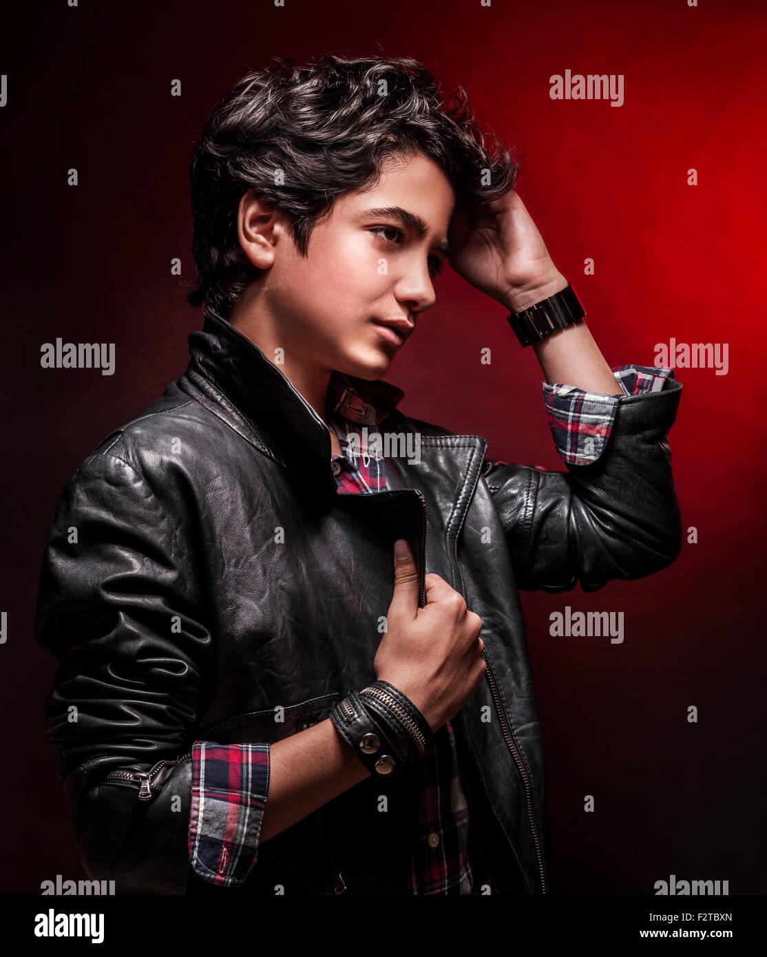 Portrait Of Teen Boy Wearing Leather Jacket And Touching His Stylish