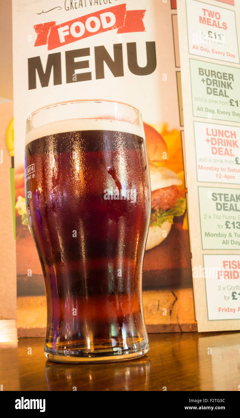 Pint of beer with food menu in traditional pub in England UK Stock Photo