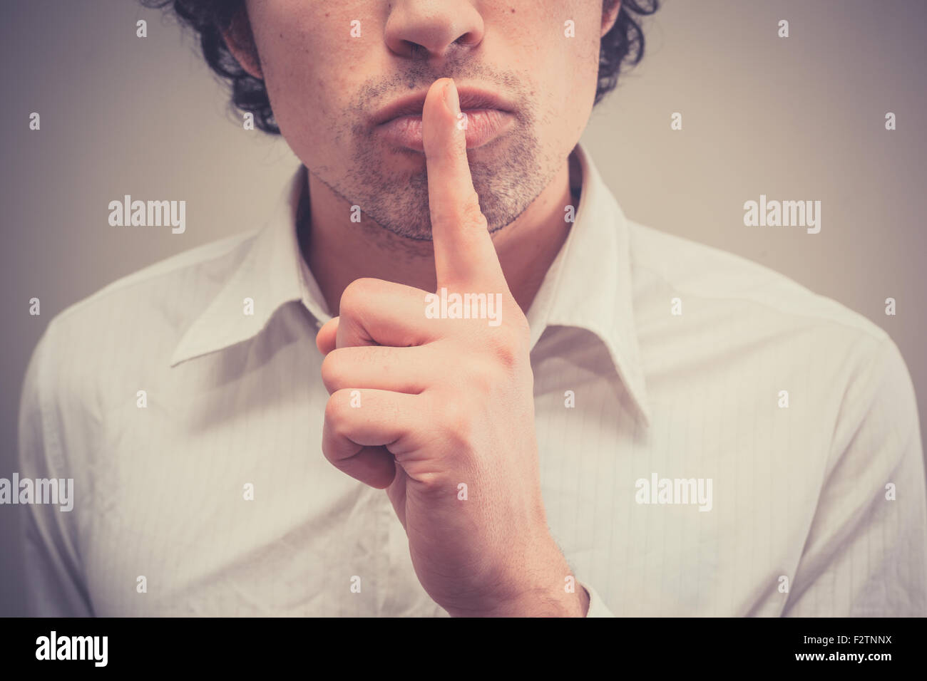 Young man with finger on lips is gesturing hush - Stock Image