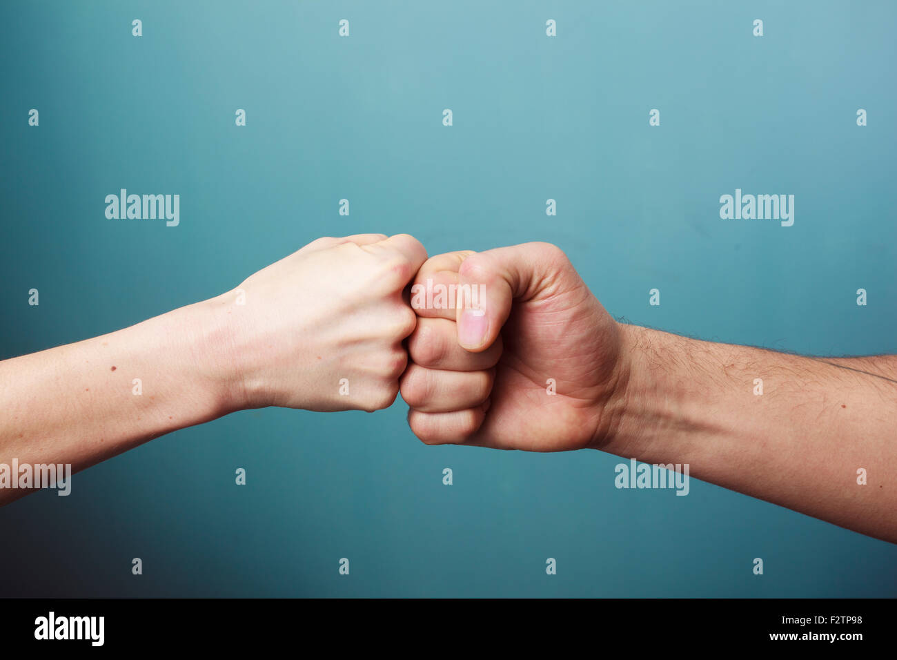 Young man and woman are fist bumping - Stock Image