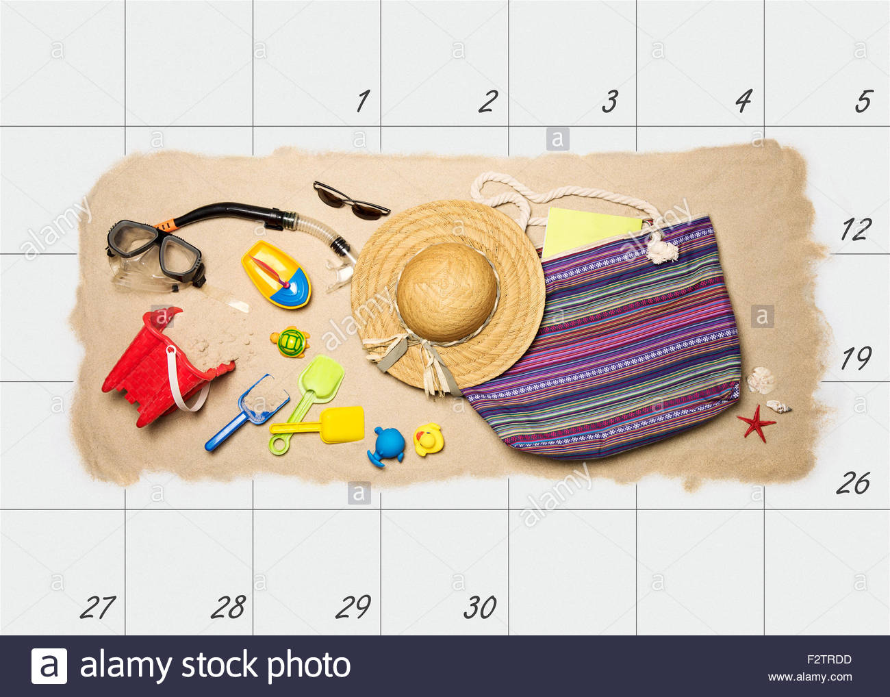 Summer holiday planning. Summer beach accessories on top of monthly calendar - Stock Image