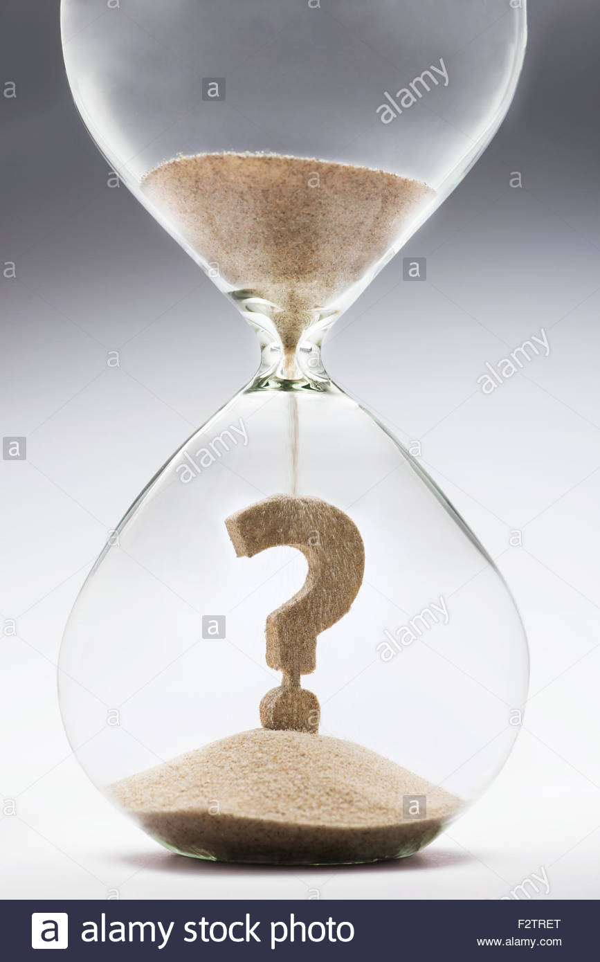 Future uncertainty. Question mark made out of falling sand inside hourglass - Stock Image