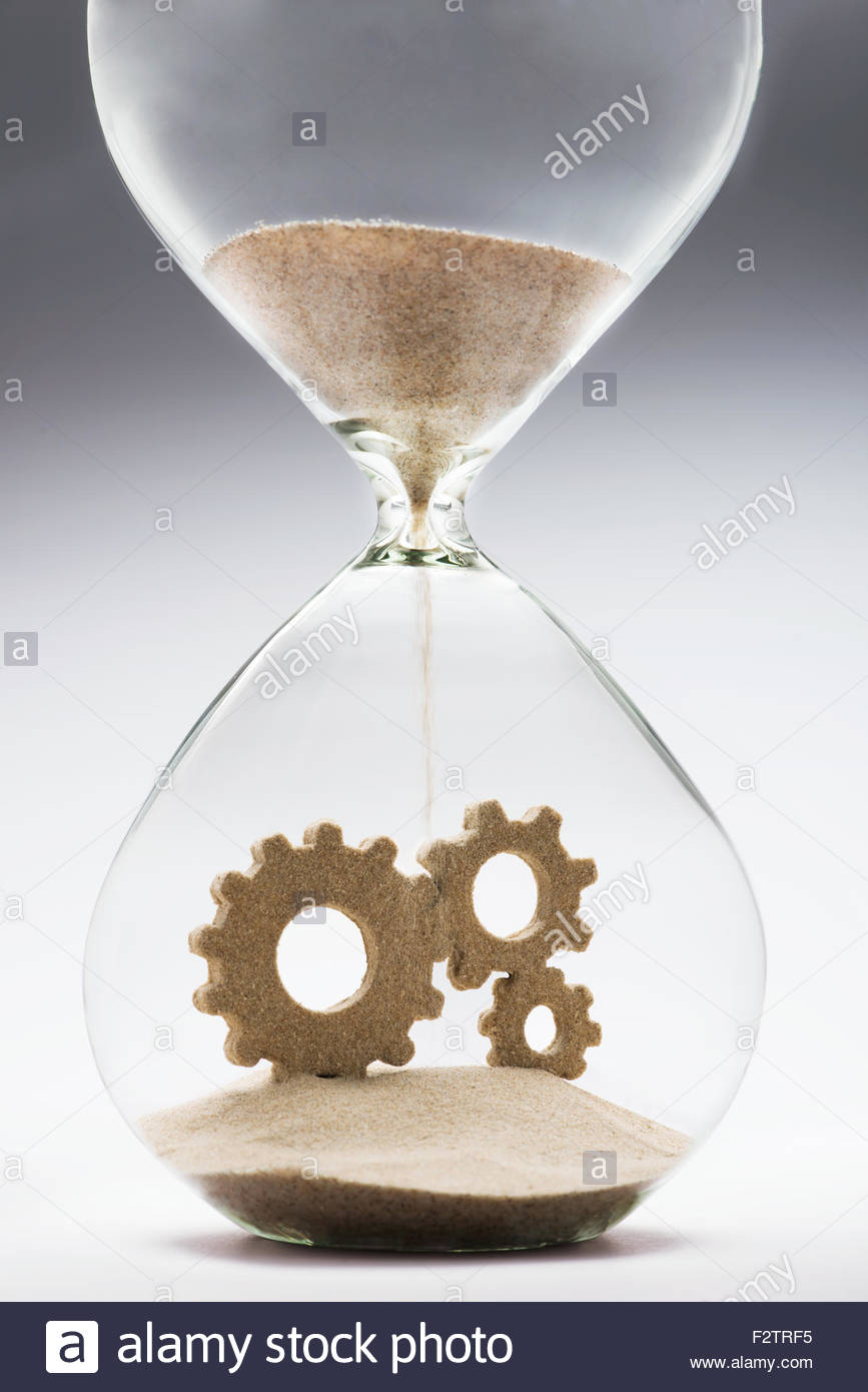 Connected gears made out of falling sand inside hourglass - Stock Image